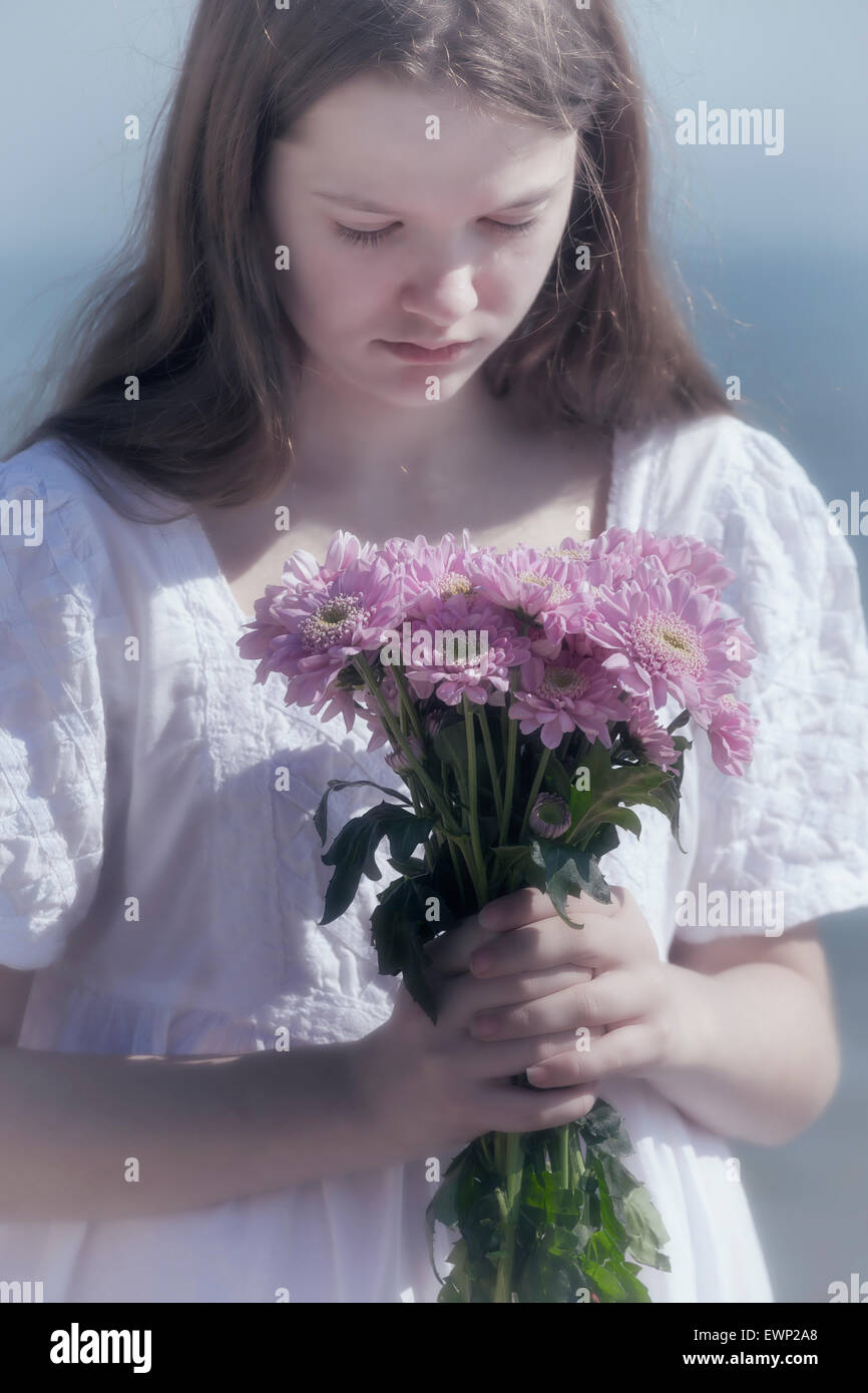 a girl holding a bouquet of flowers - Stock Image