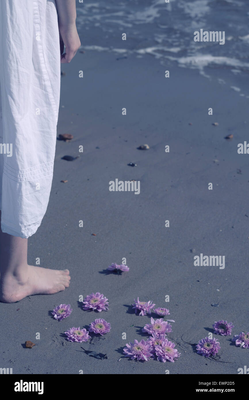 a girl in a white dress is standing next to pink blossoms on a beach - Stock Image