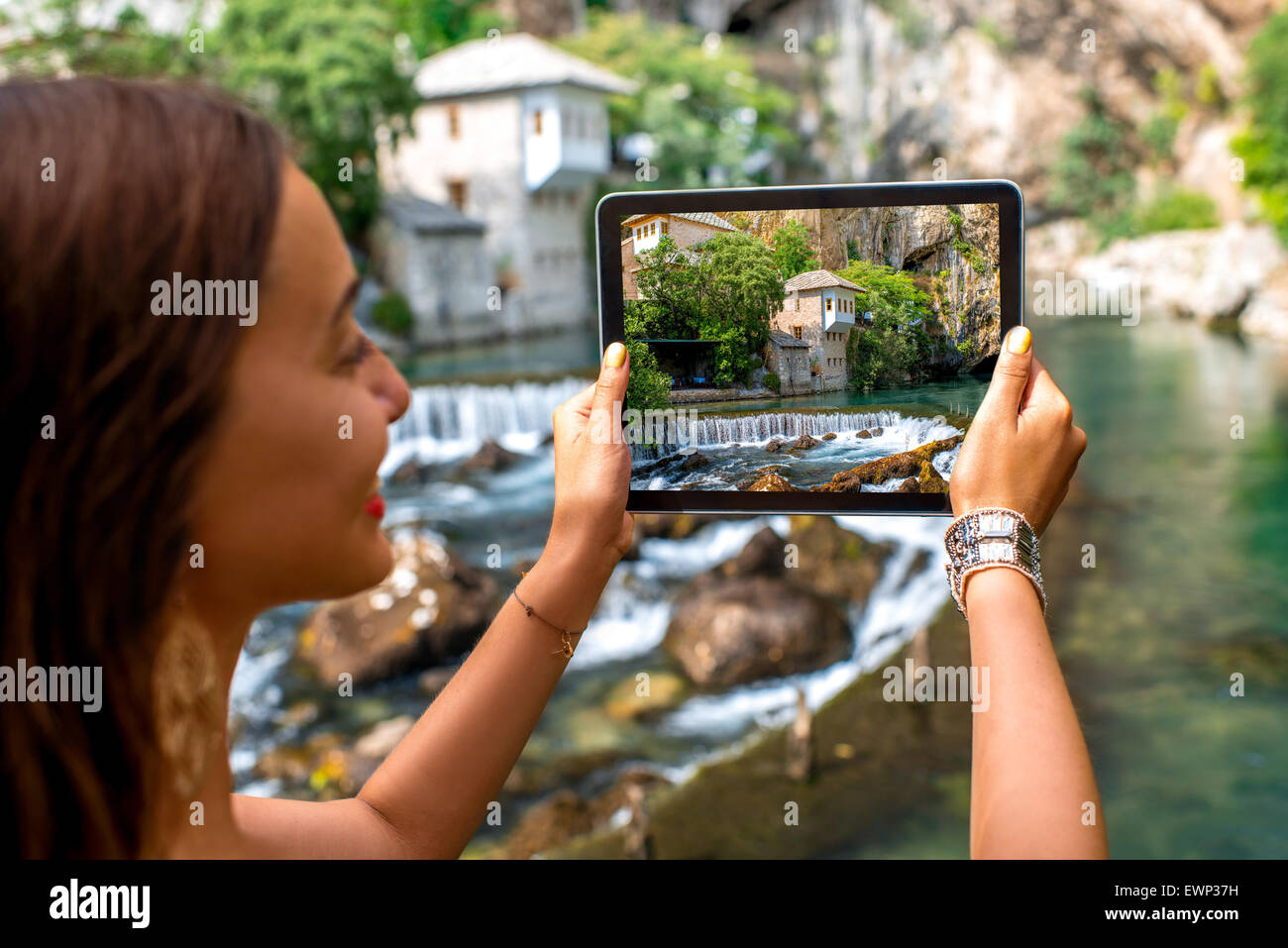 Woman photographing house on Buna spring in Blagaj village - Stock Image