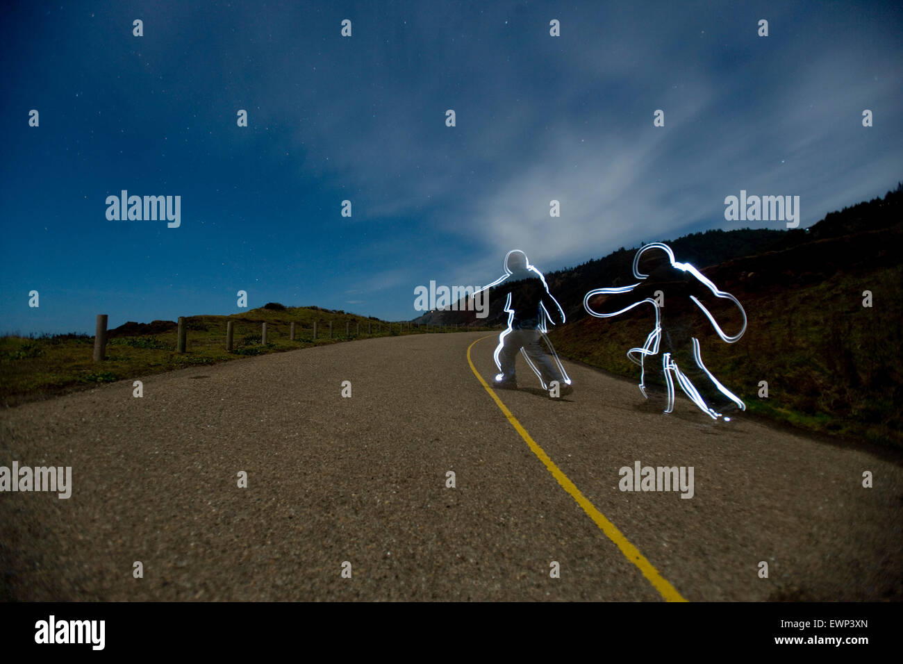 Lightpainting image of two humans walking across a road - Stock Image