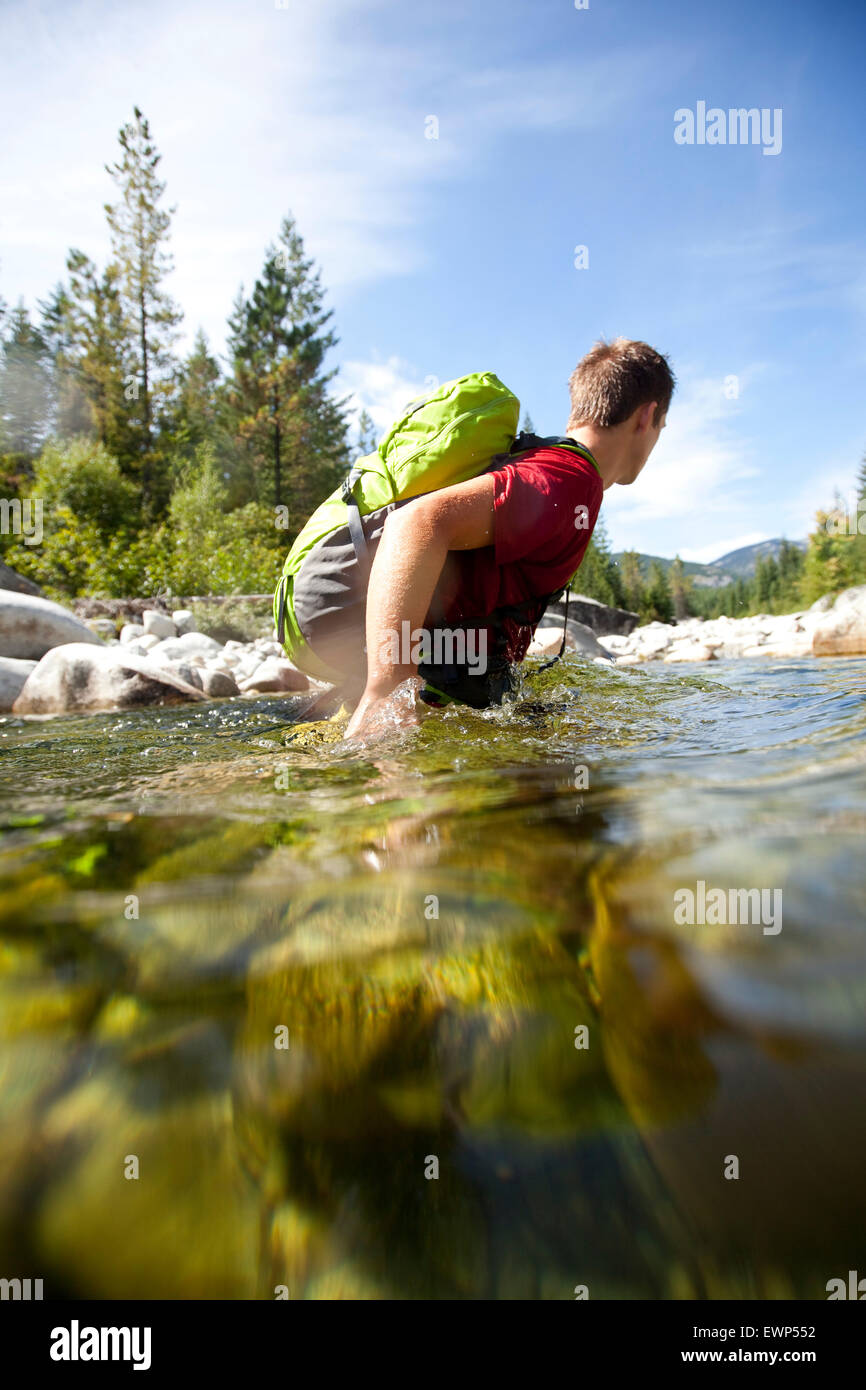 Young adult man fording a deep section of a river wearing a day pack - Stock Image
