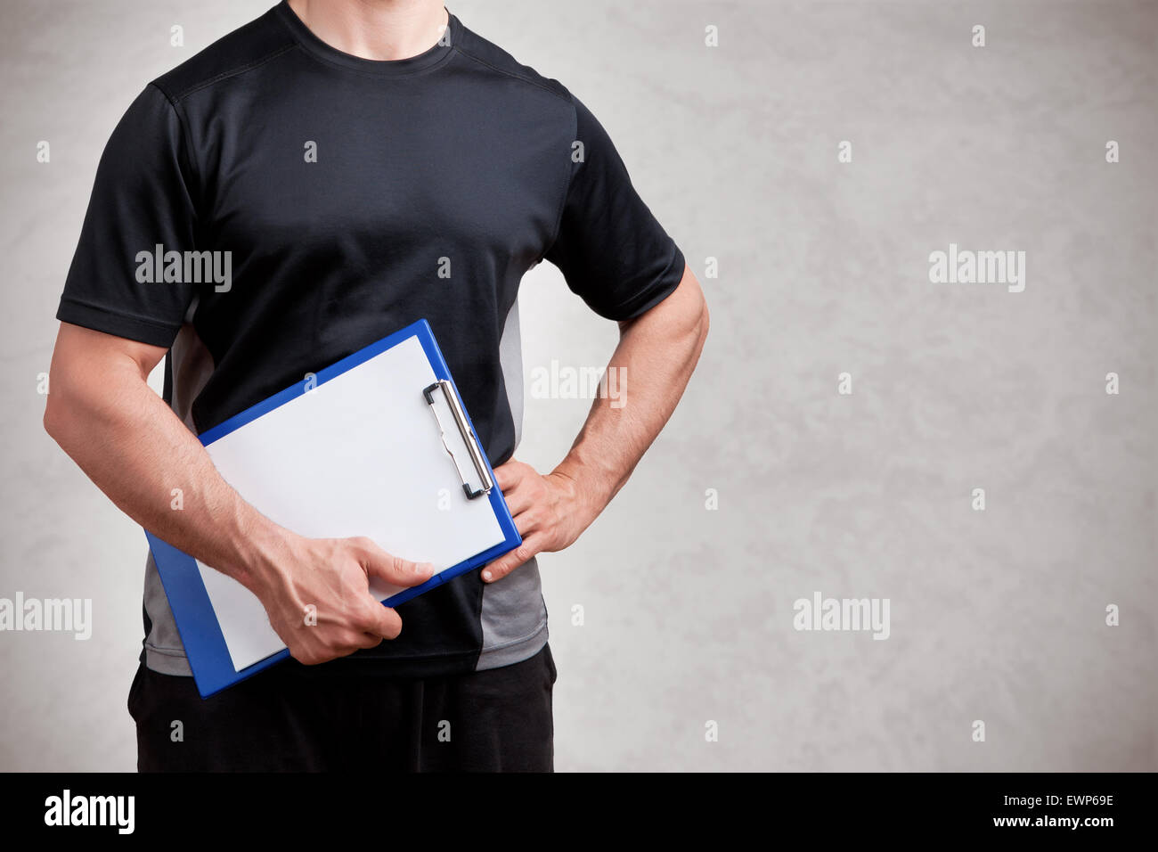 Personal Trainer, with a pad in his hand, isolated in grey - Stock Image