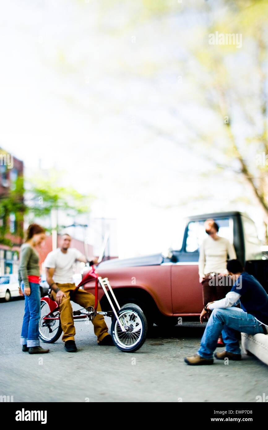 Group of twenty somethings hanging out on the street next to an old truck - Stock Image