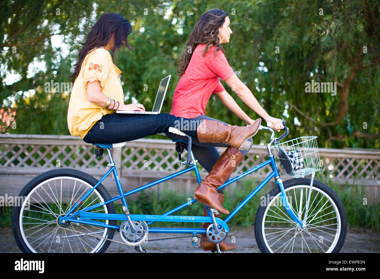 Two women riding a tandem bike while the woman on back surfs the internet on a laptop - Stock Image