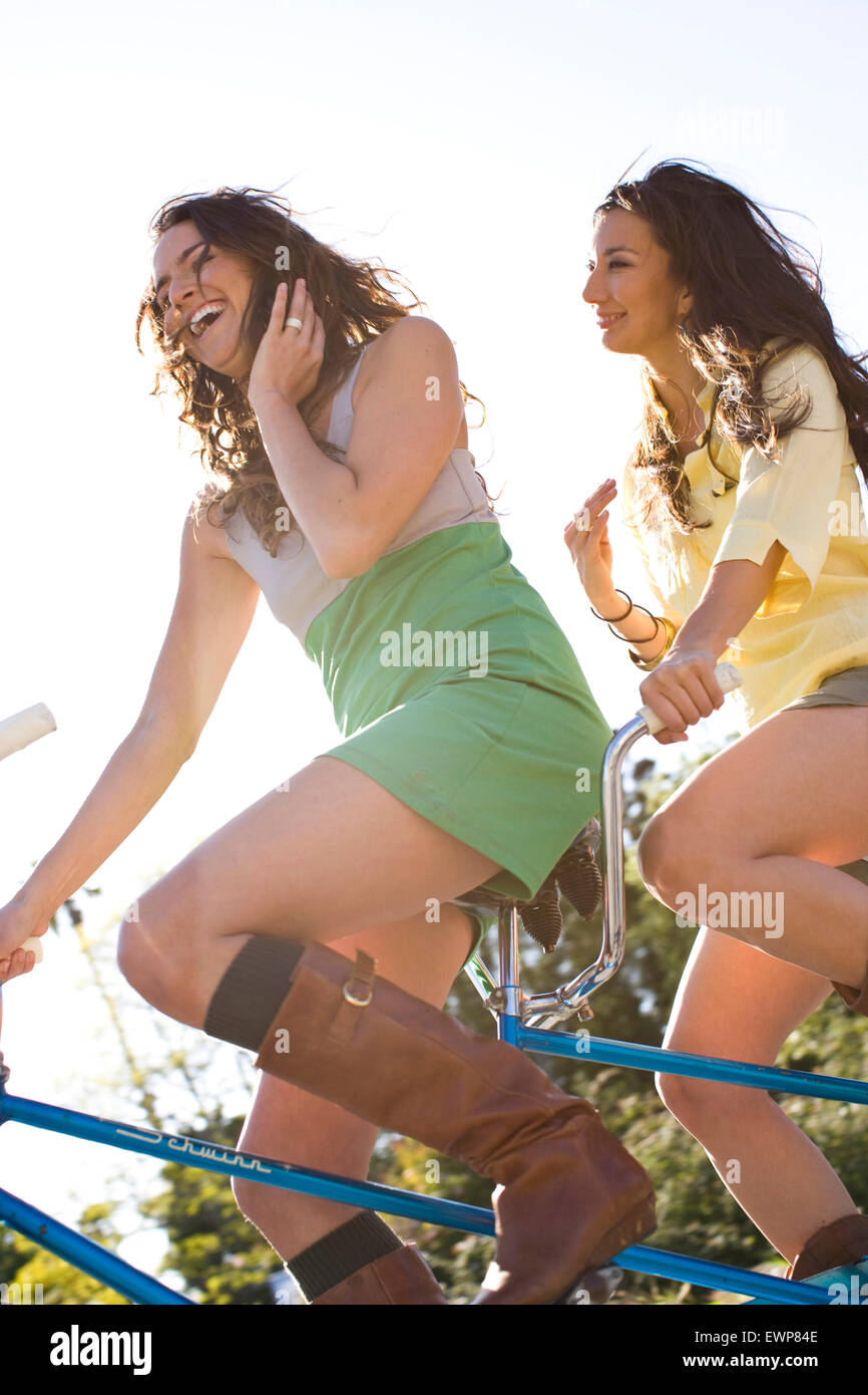 Portrait of two twenty something women riding a tandem bike. - Stock Image