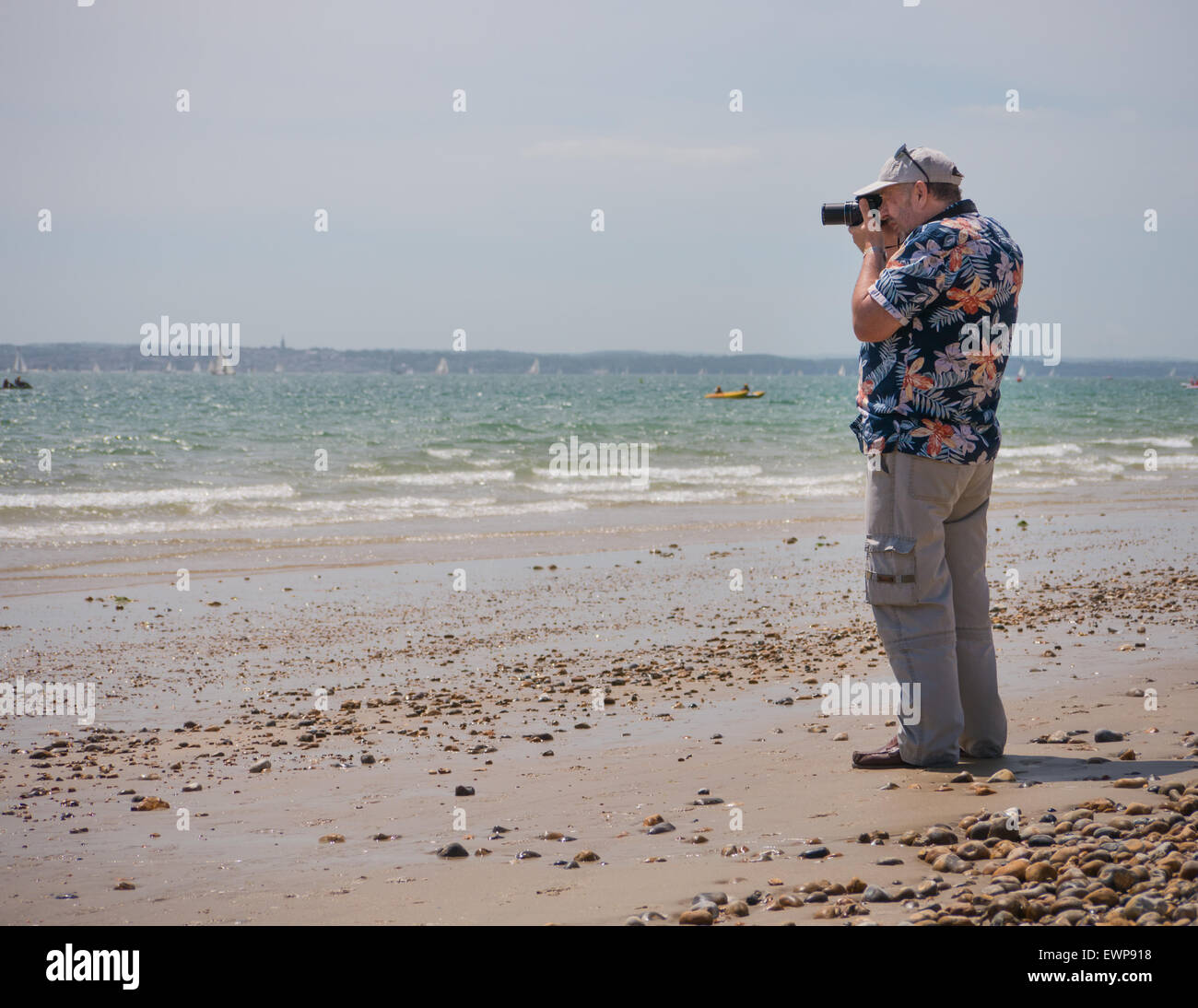 0220da04068b A photographer in a Hawaiian shirt take photographs on the beach - Stock  Image