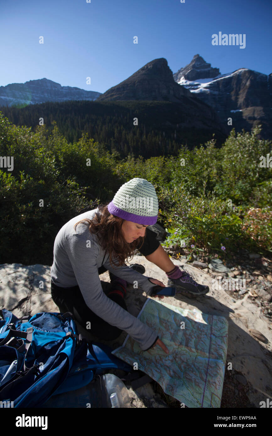 A woman reading a map in the high country. - Stock Image