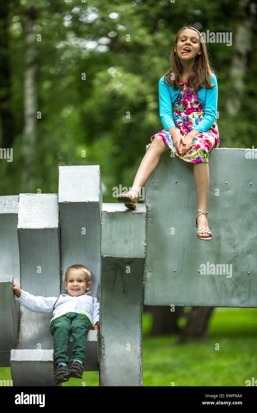 Girl with her little brother on the Playground in city Park. Stock Photo