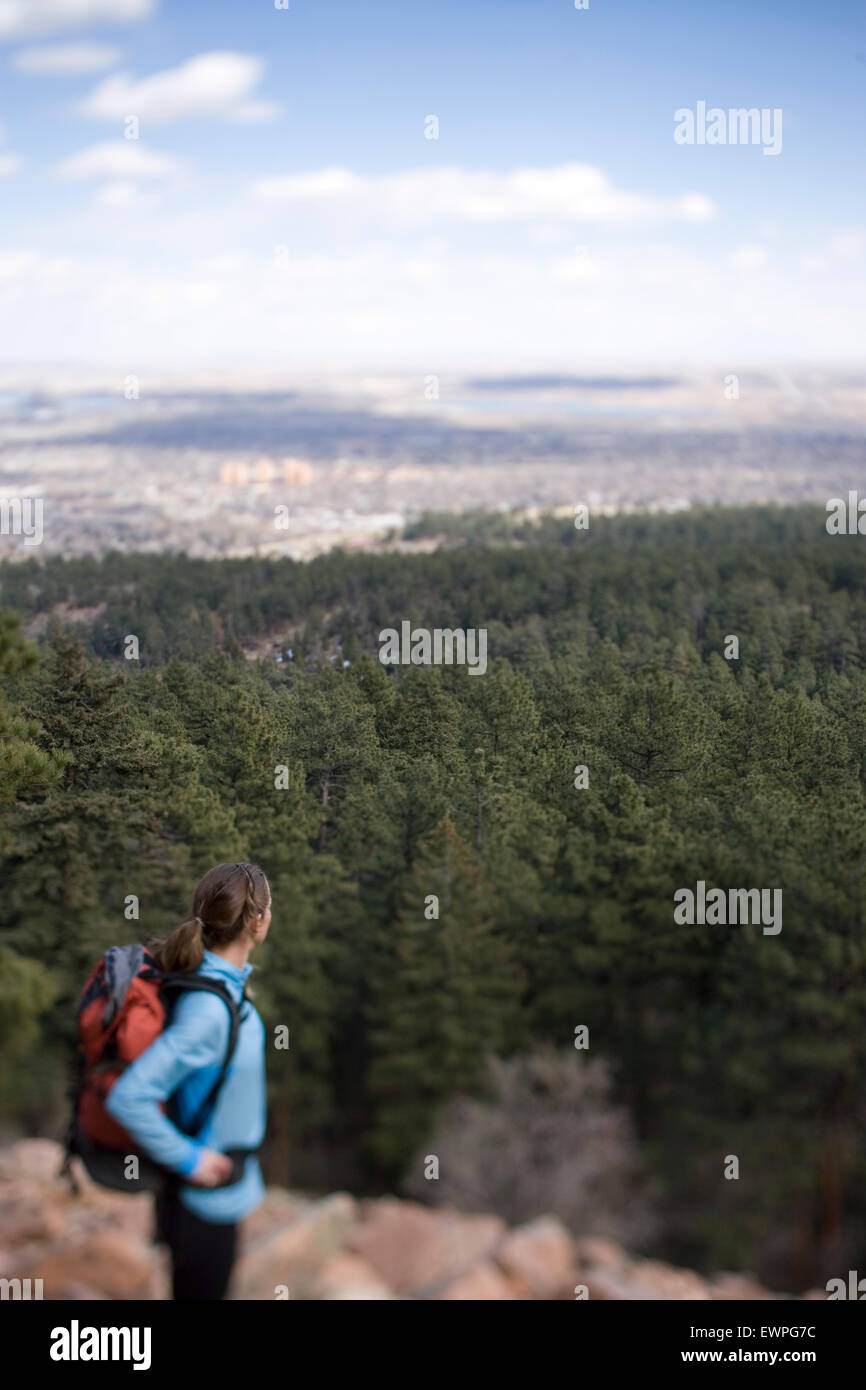Portrait of woman dayhiking with view of urban sprawl in background - Stock Image