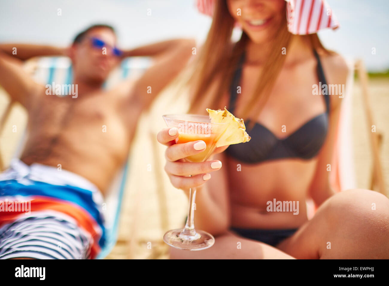 Glass of refreshing tropical cocktail held by young girl in bikini - Stock Image