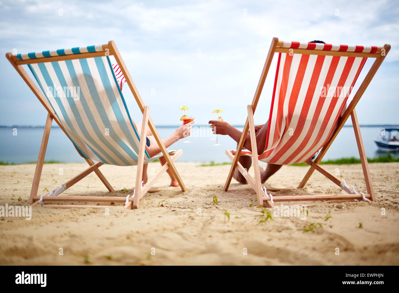 Restful couple toasting with cocktails on the beach - Stock Image