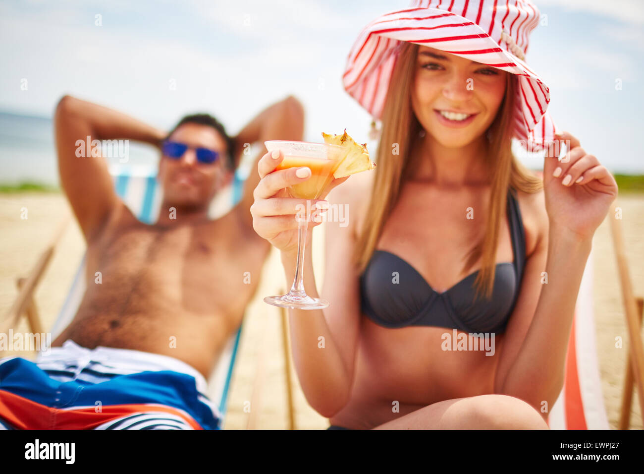 Pretty girl in hat holding tropical cocktail - Stock Image