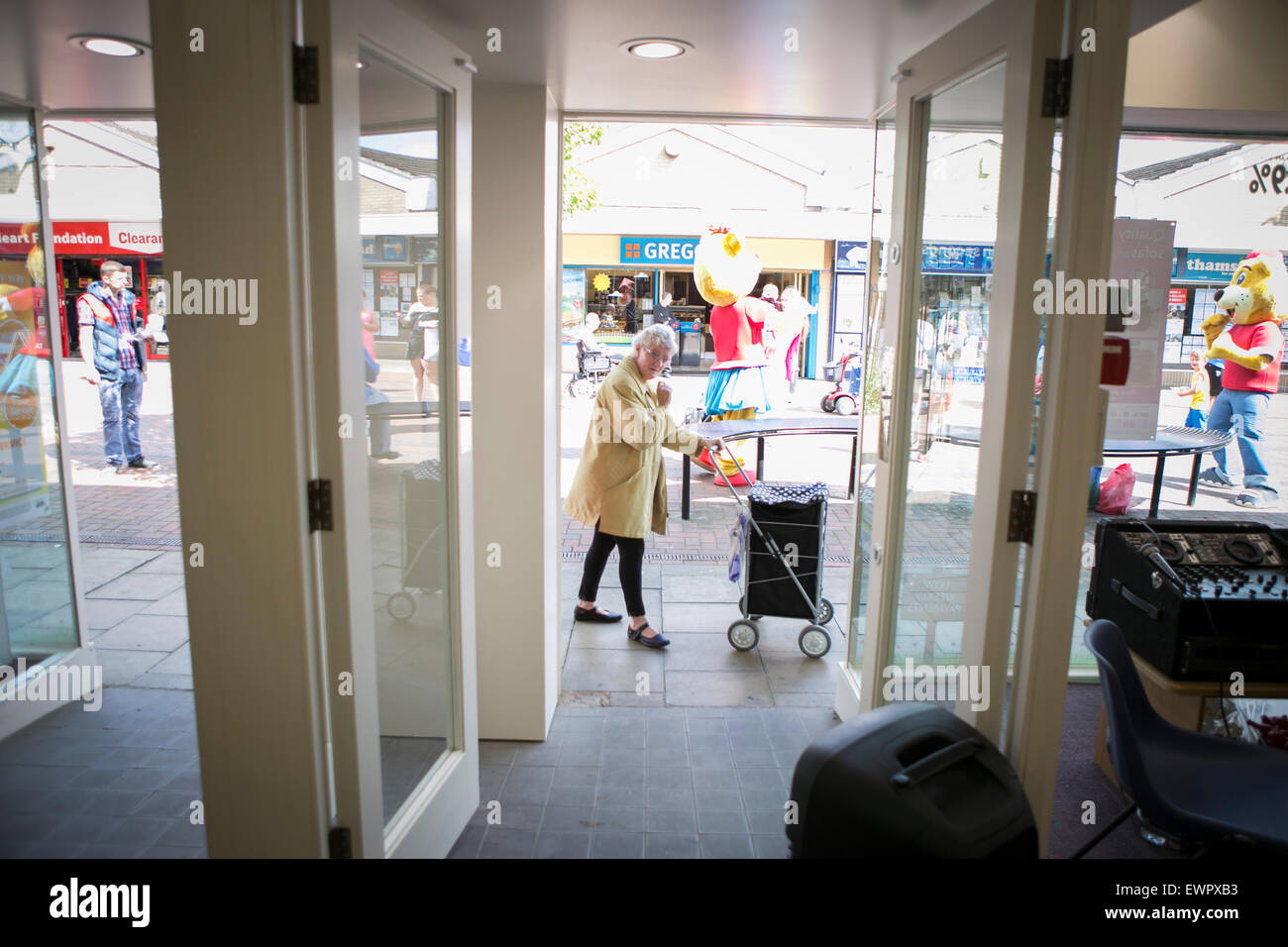 A woman with a shopping trolley walks past an open shop door - Stock Image