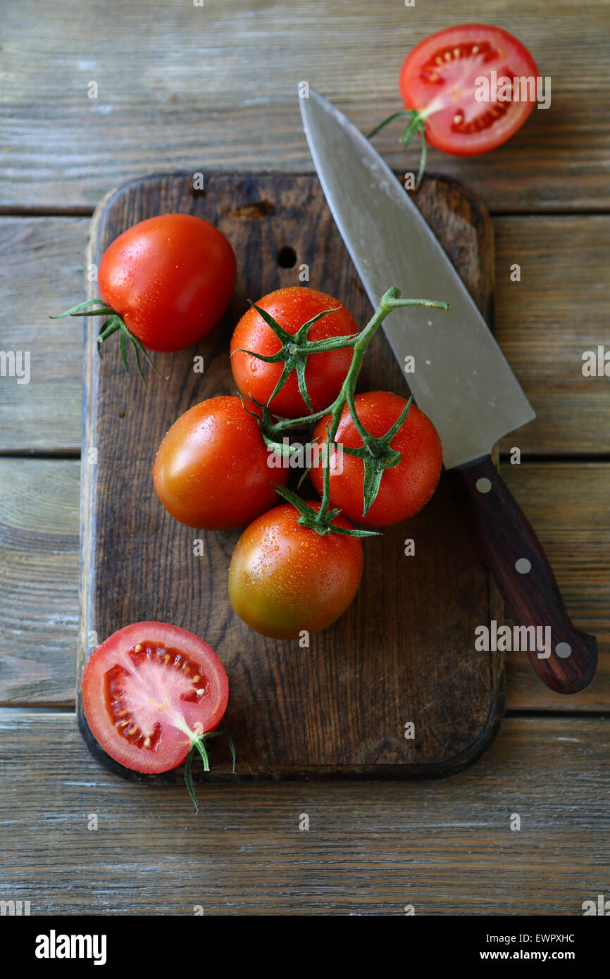 tomatoes on the old cutting board, food top view - Stock Image
