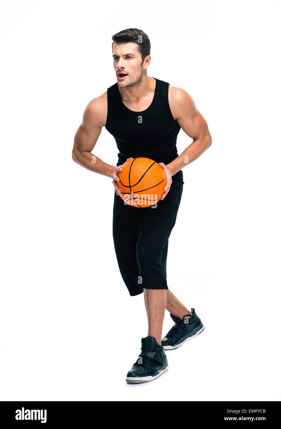 Full length portrait of a handsome man im sports wear playing in basketball isolated on a white background - Stock Image