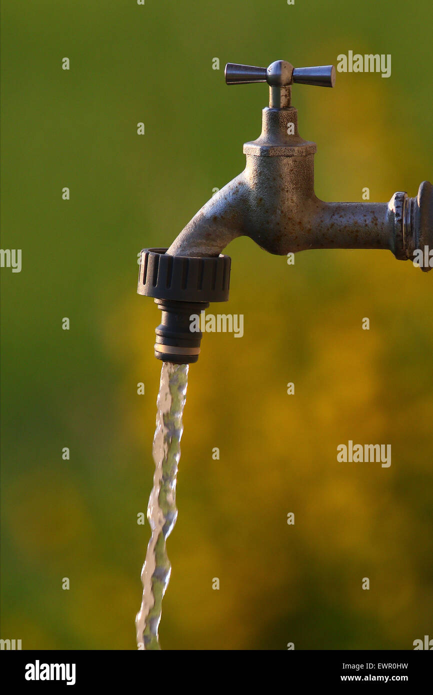 Fresh clean water spilling out of a faucet with a colorful background - Stock Image