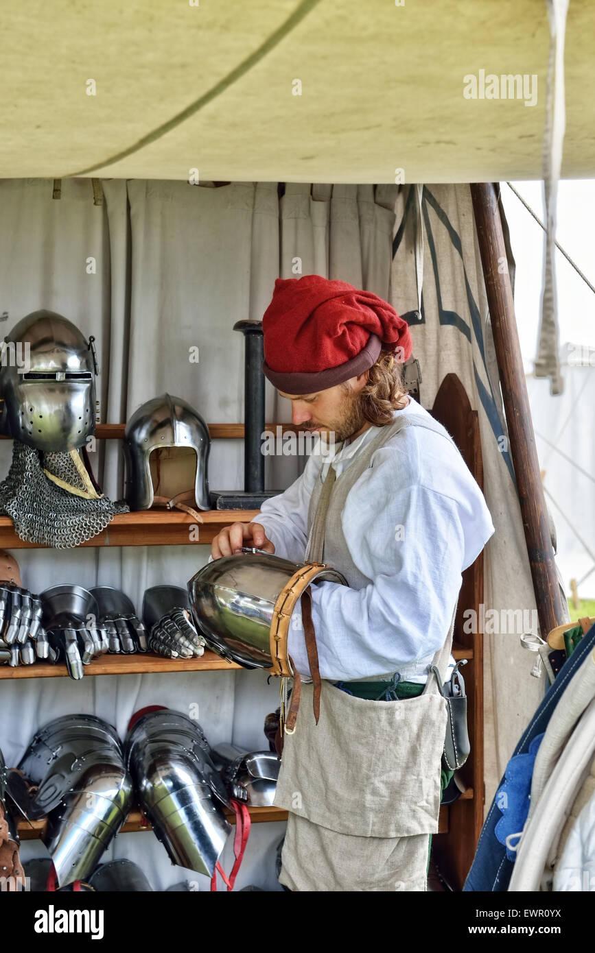 DEURNE, BELGIUM-JUNE 13, 2015: Unidentified participant of medieval market reconstructions prepares casques and - Stock Image