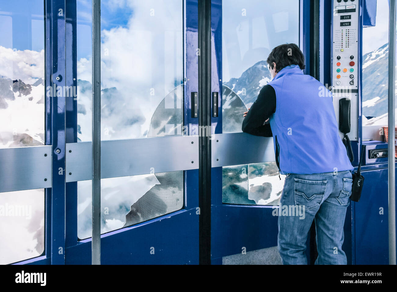 Lift operator in Pic du Midi cable car travelling up to summit - Stock Image
