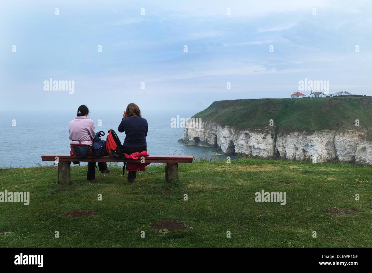 Couple on seat overlooking Thornwick Bay and Flamborough on the Yorkshire coast. Stock Photo