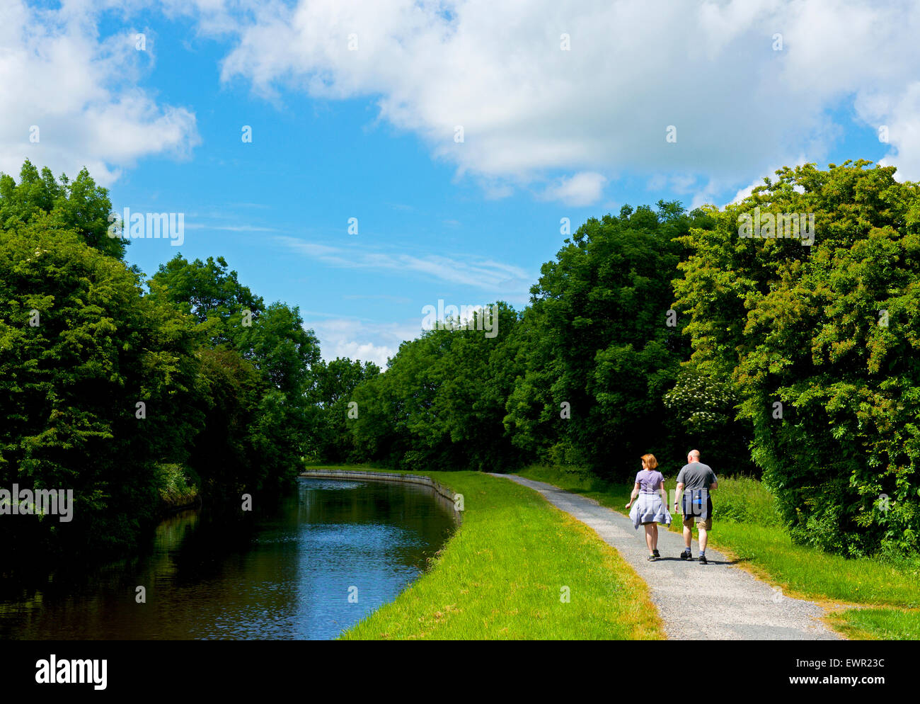 Couple walking on the towpath of the Leeds and Liverpool Canal near Barnoldswick, Lancashire, England UK - Stock Image