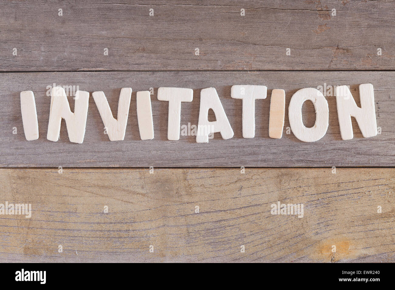 Word invitation over a wooden background - Stock Image