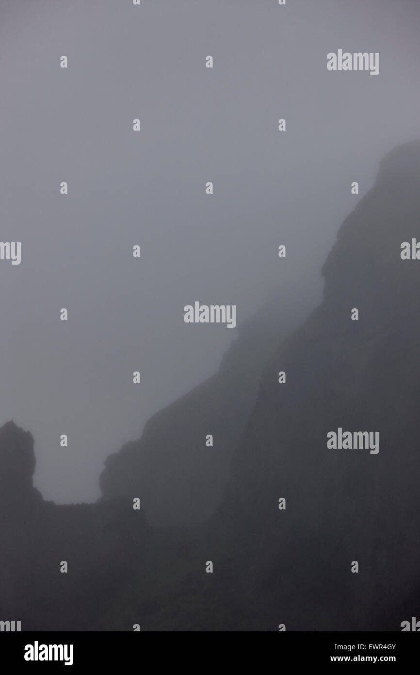 low mist and cloud limited visibility in the mountains with troll faces in the rock Iceland - Stock Image