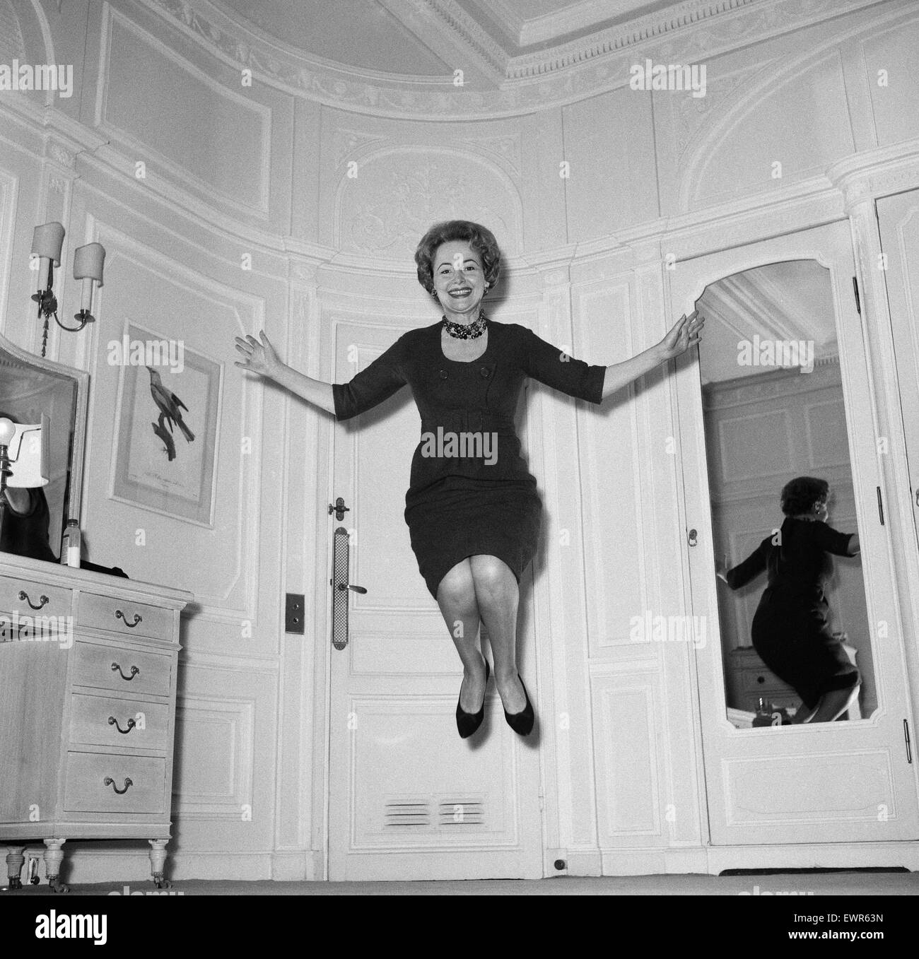 Olivia De Havilland playing a jumping game with her husband. 20th November 1959. - Stock Image