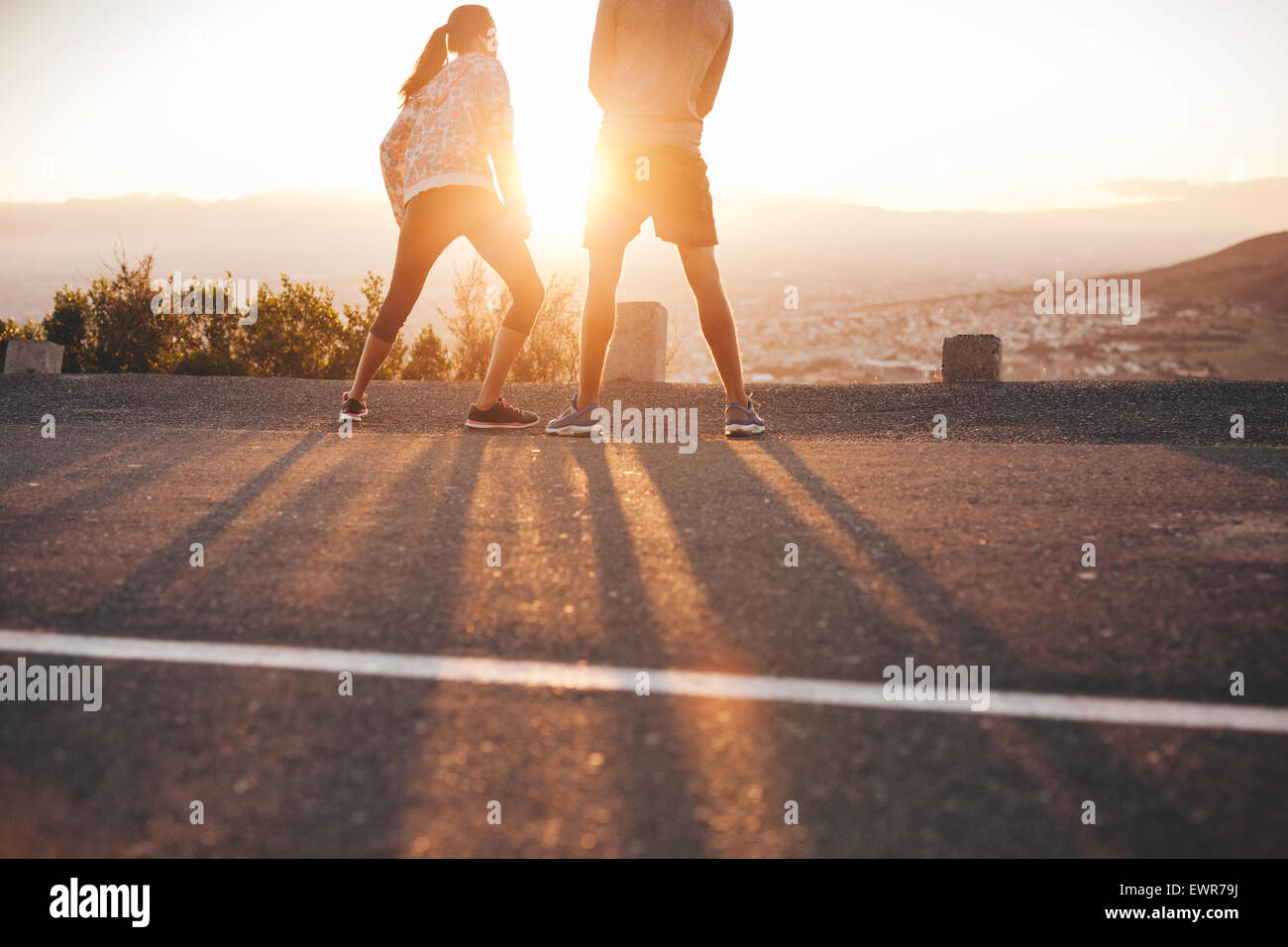 Rear view of young couple standing on hillside in morning facing the sun light. Young woman stretching her legs - Stock Image