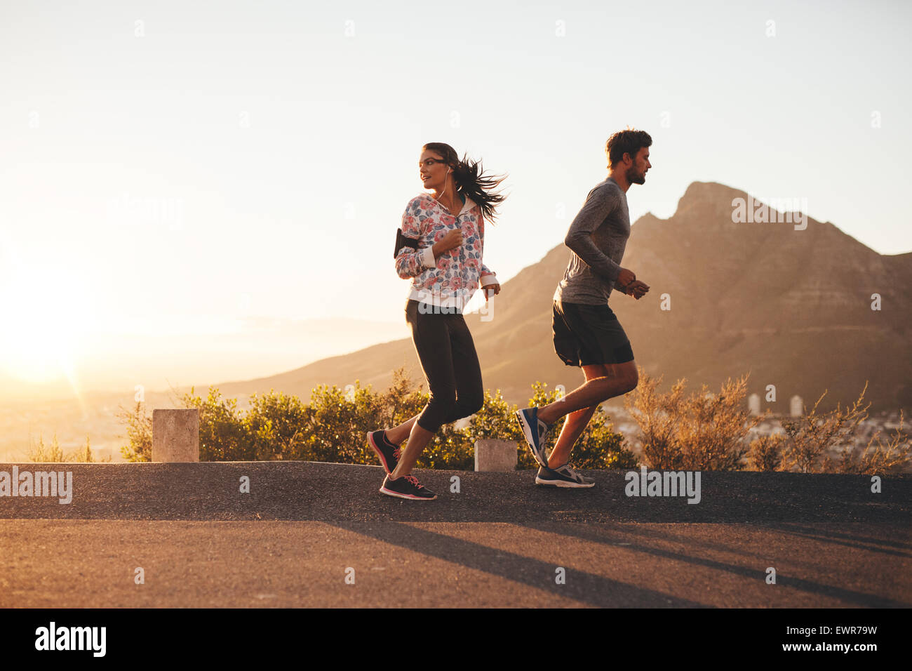 Young couple jogging early in morning, with woman looking back over her shoulder. Young man and woman running outdoors Stock Photo