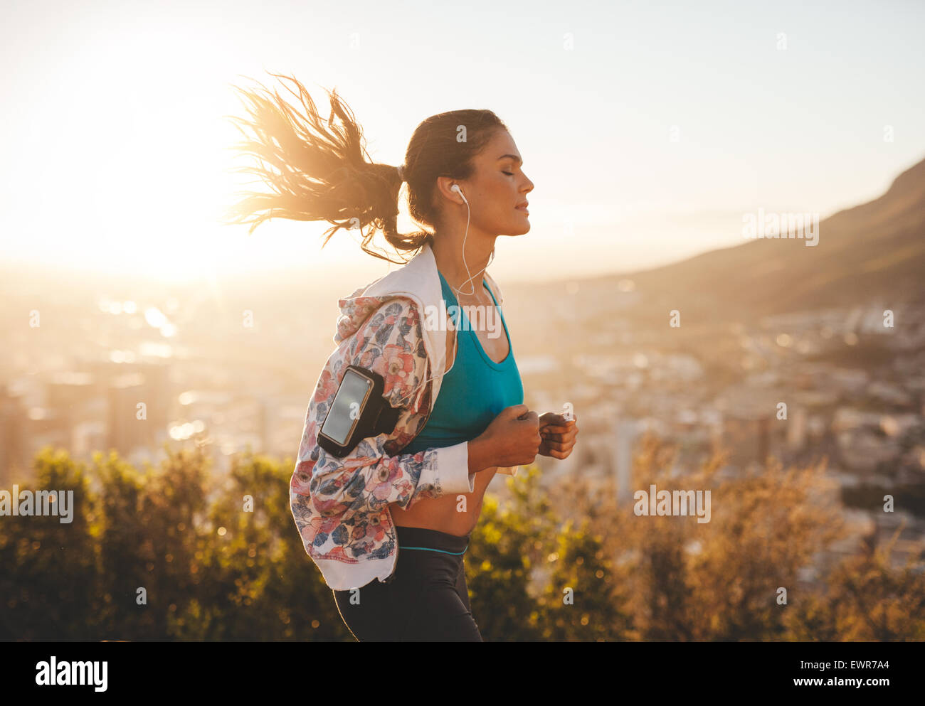 Portrait of beautiful young woman out for a run on a hot sunny day. Caucasian female model jogging outdoors. - Stock Image