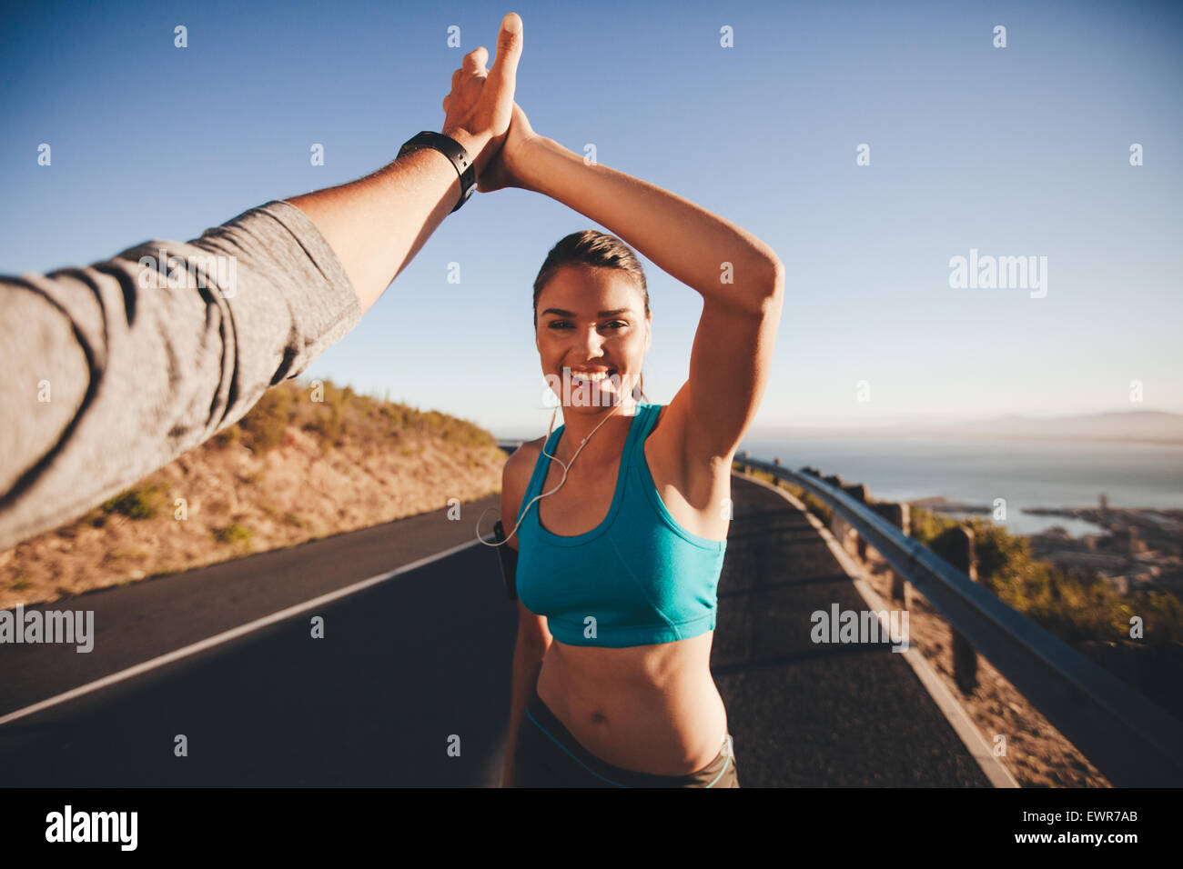 First person view of a man and woman doing a high five. Happy young woman giving high five to man after outdoor - Stock Image