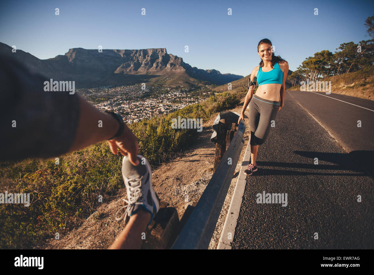 Fit young woman standing with man stretching his leg outdoors on country road. Young runners relaxing after morning - Stock Image