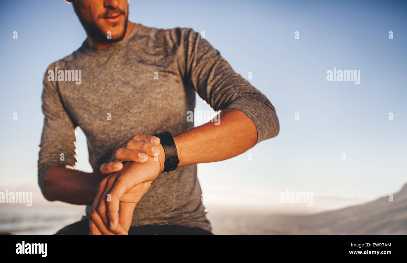 Male athlete checking time while on outdoor training. Young runner checking the time on his sport swatch - Stock Image