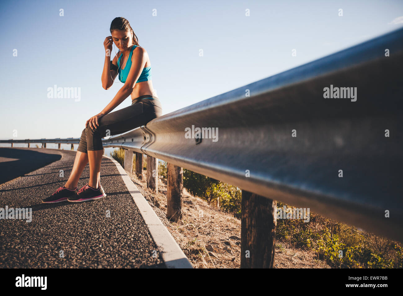 Outdoor shot of young female athlete taking break from running workout, adjusting her earphone. Sports woman sitting - Stock Image