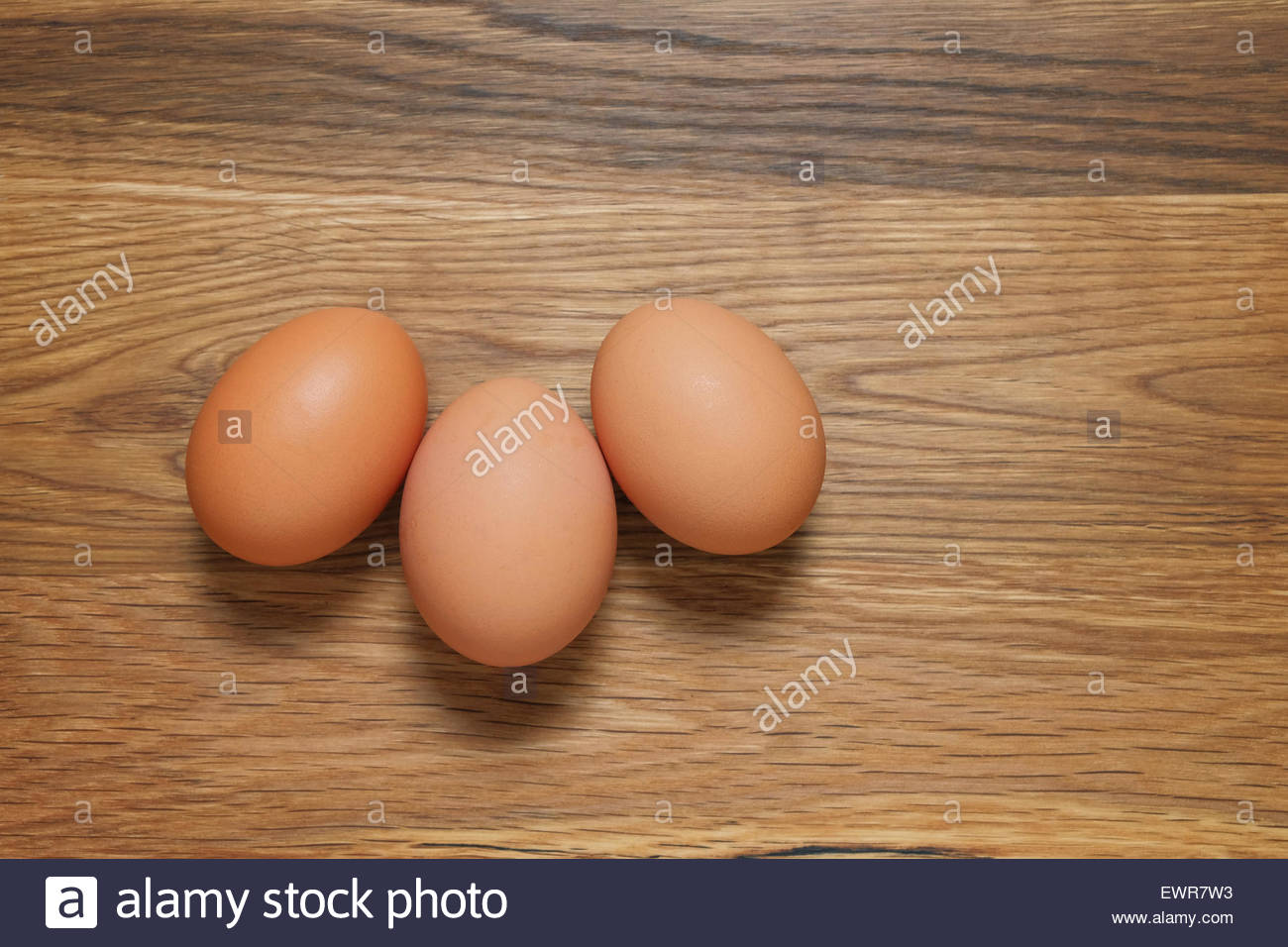 Three brown hens eggs shot from above on a wooden table - Stock Image