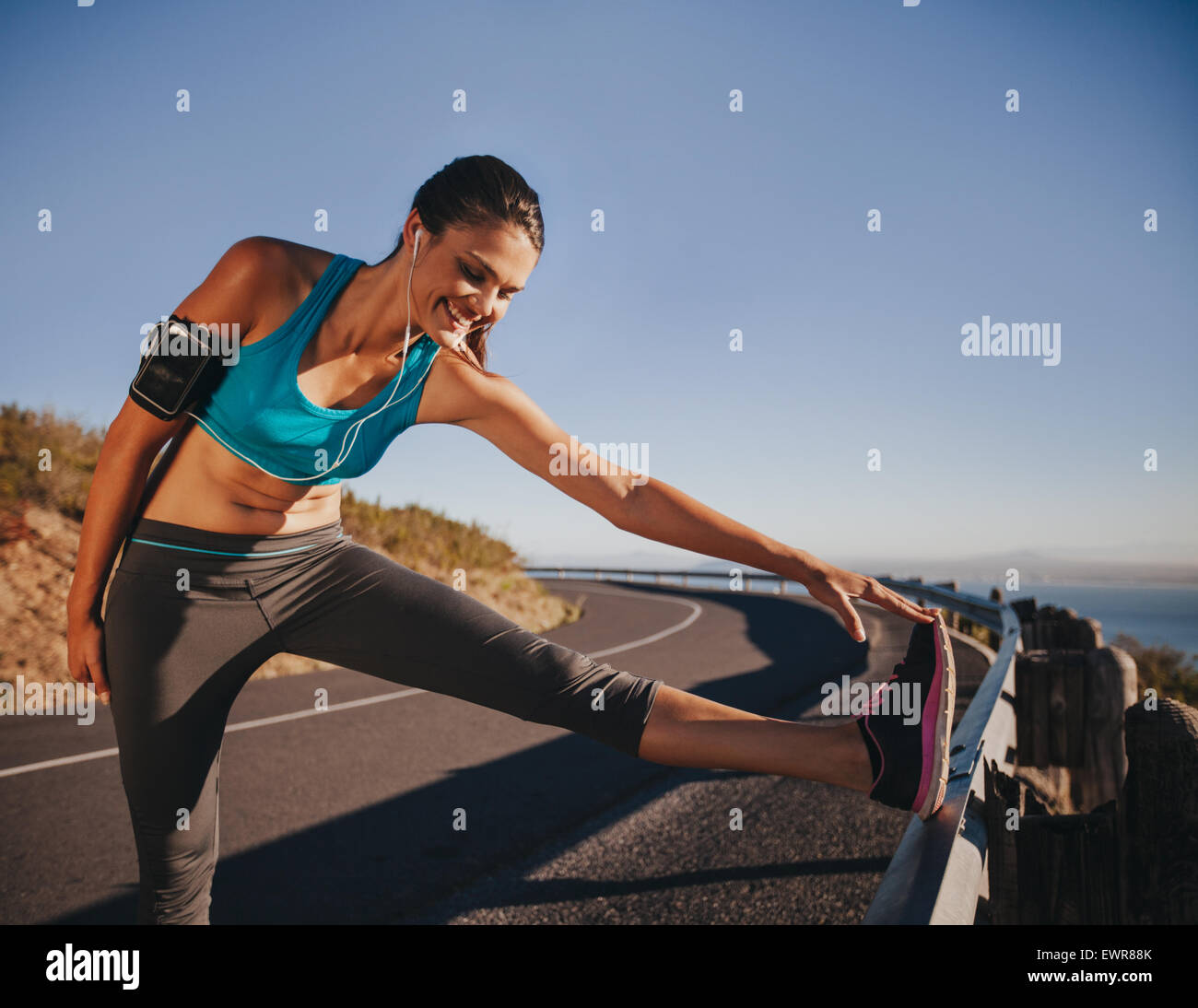Sports woman stretching her leg on a guardrail before running outdoors. Female athlete getting ready for a run. - Stock Image