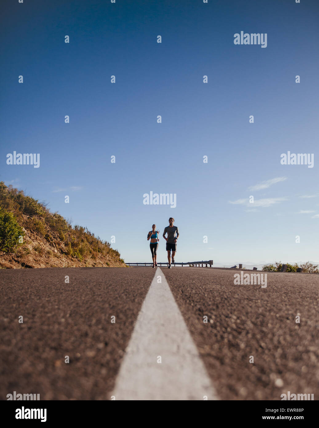 Low angle shot of two young runners training together on the road. Morning run on country road on a summer day with - Stock Image