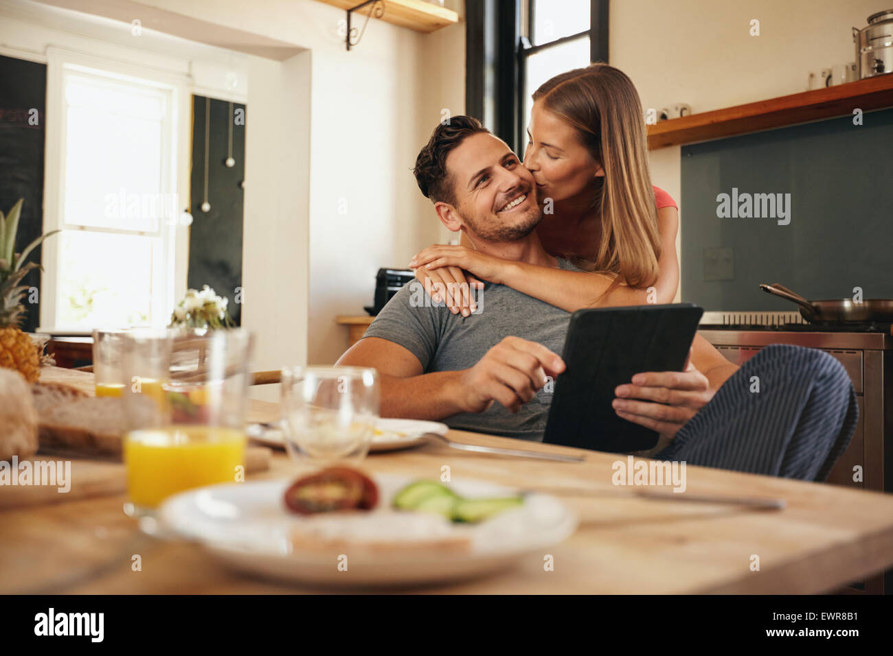 Young man holding a digital tablet while his girlfriend hugs him from behind, giving him a good morning kiss. Young - Stock Image