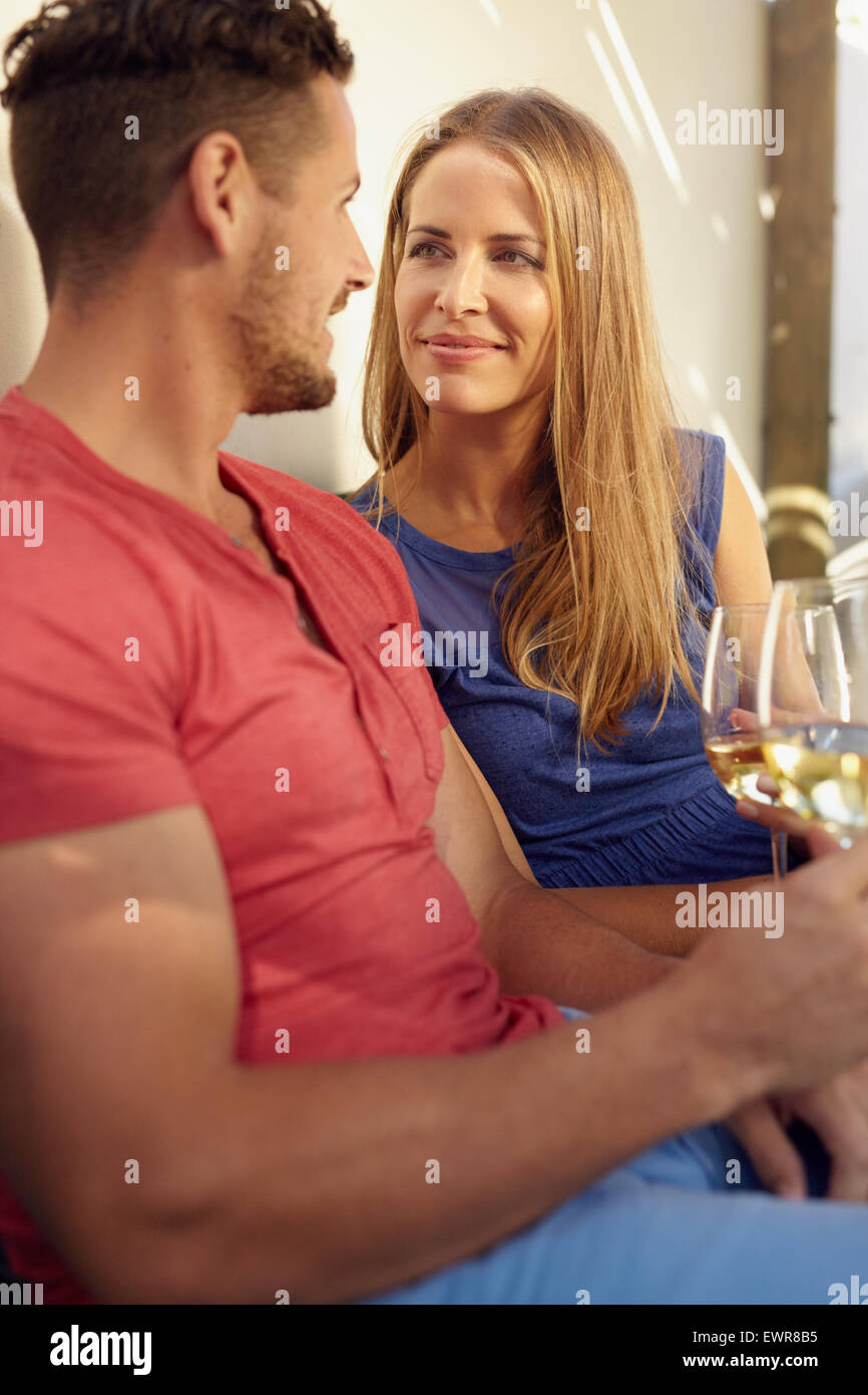 Loving young couple holding a glass of wine, looking at each other romantically. - Stock Image