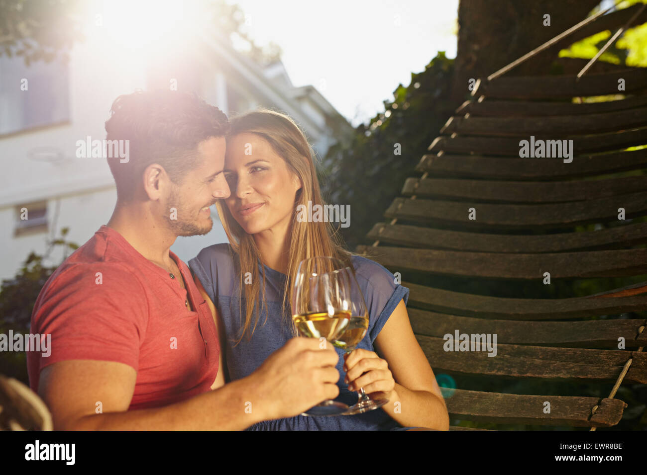Romantic young couple sitting on garden hammock toasting wine. Loving young couple celebrating with a glass of wine - Stock Image