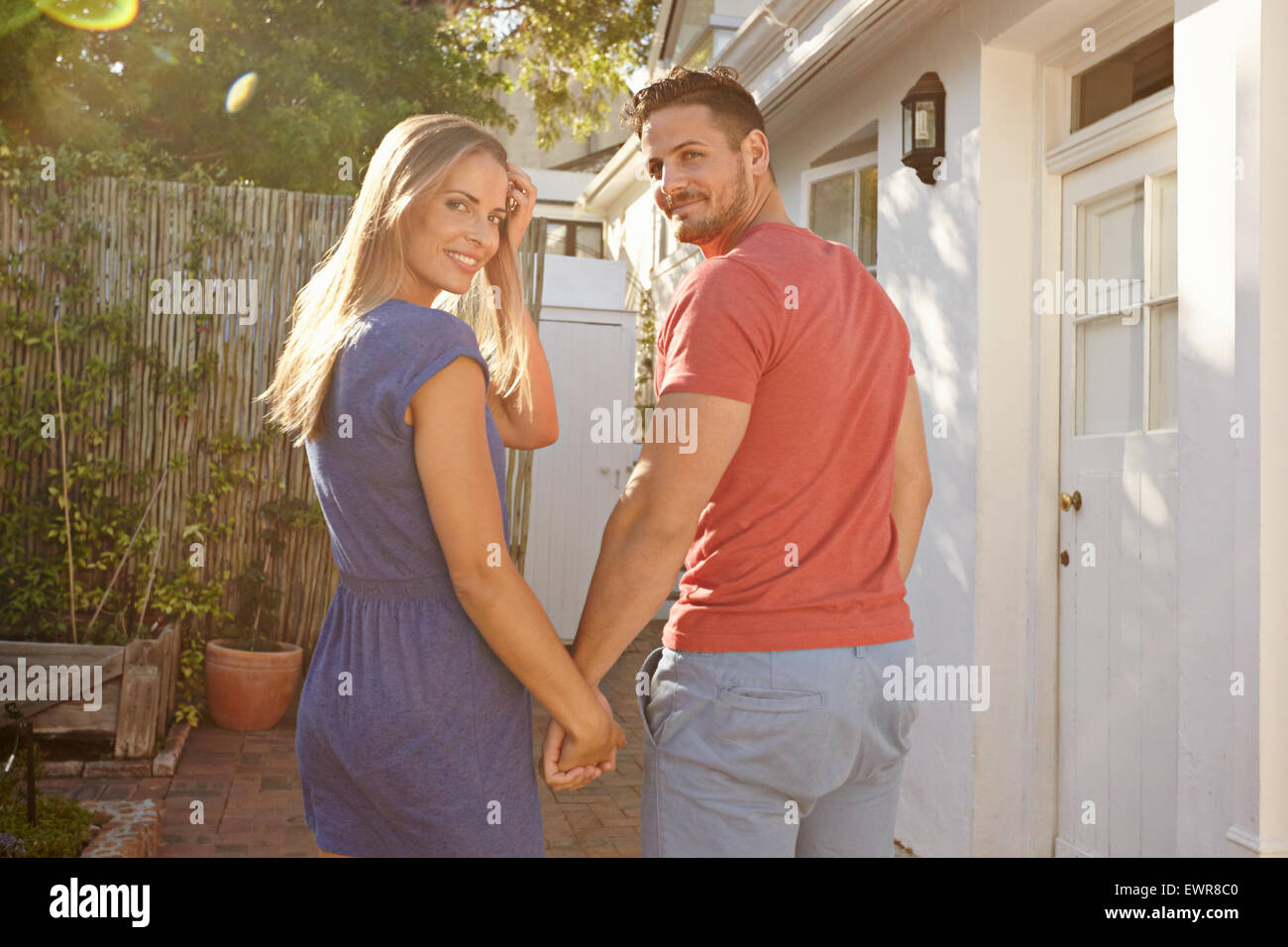 Outdoor shot of young caucasian couple walking to their house holding hands, both looking back over shoulder and - Stock Image
