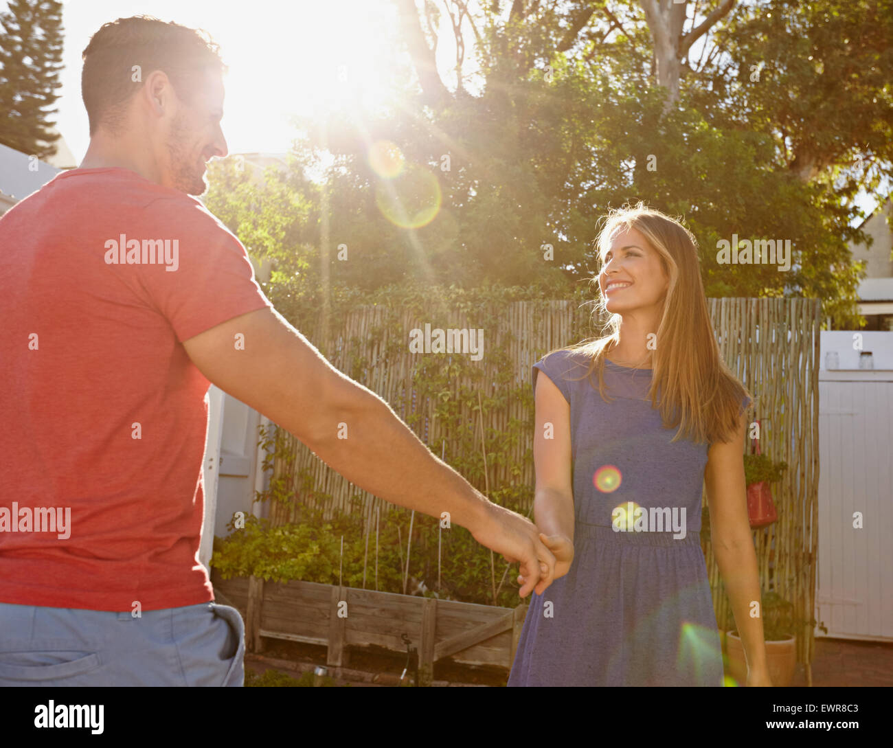 Outdoor shot of beautiful young couple standing together holding hands and looking at each other smiling. Bright - Stock Image