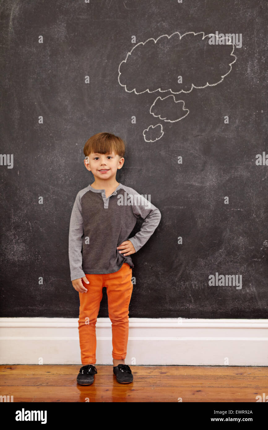Cute little boy with a thought bubble on the blackboard. Full length shot of young boy standing at home with his - Stock Image