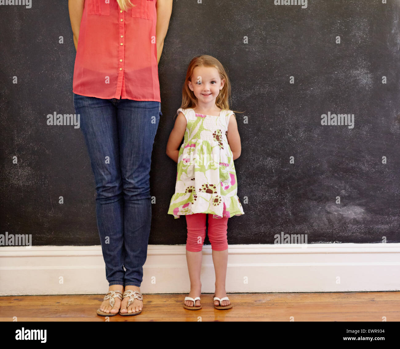 Little girl with sweet smile standing with her mother. Mother is cropped in the picture with focus on little girl - Stock Image