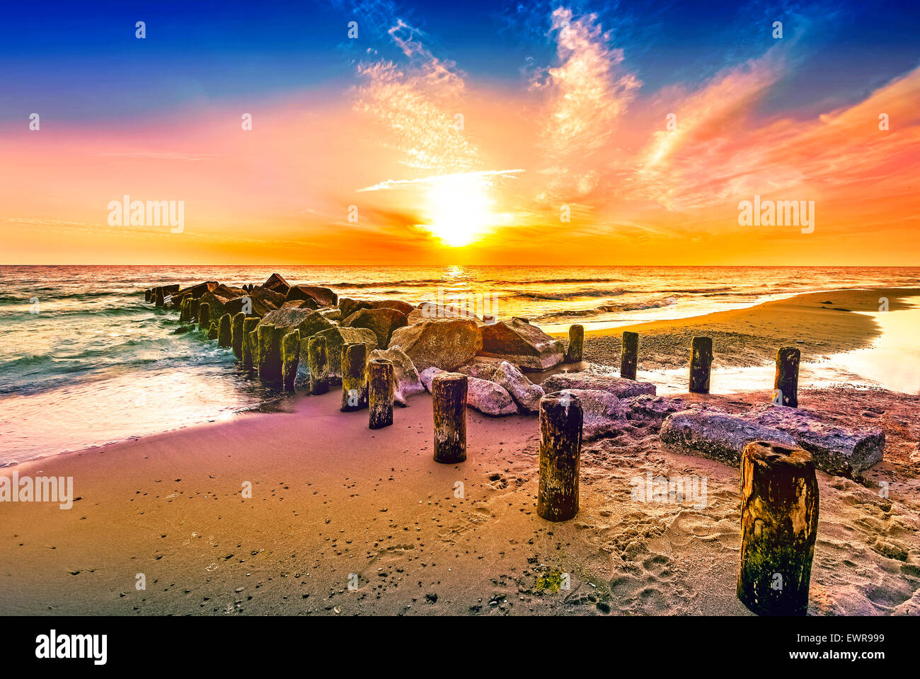 Colourful sunset on a beach. - Stock Image