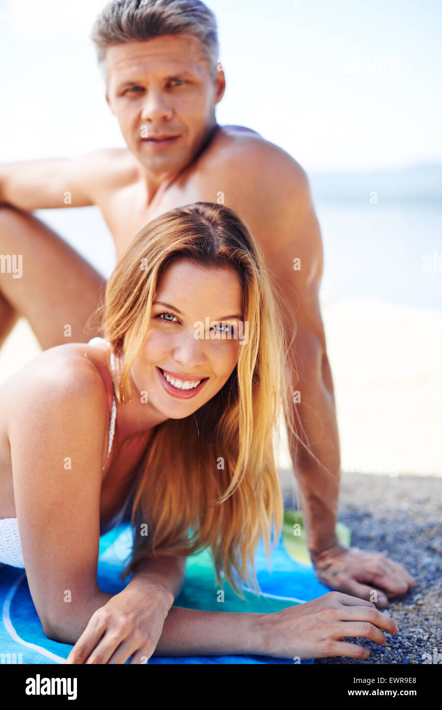 Happy young sunbather in bikini looking at camera with restful man on background - Stock Image