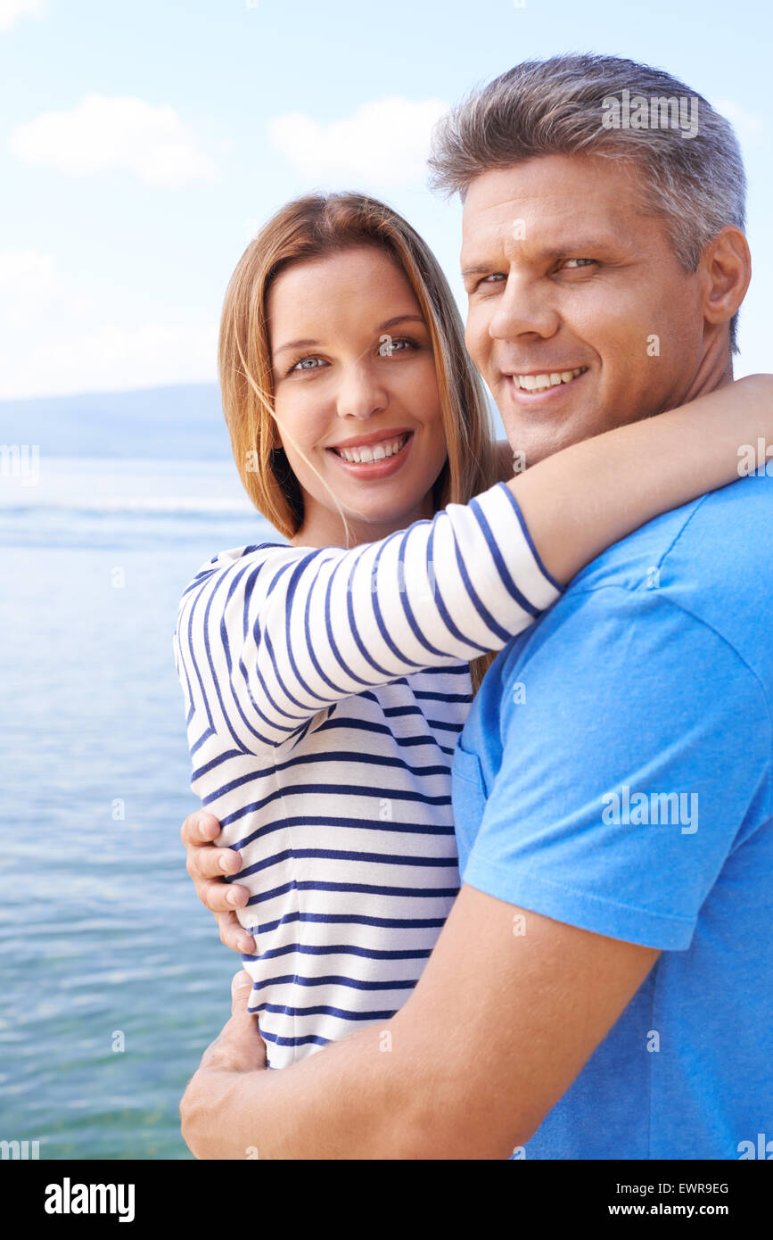 Amorous couple in embrace looking at camera by the sea - Stock Image