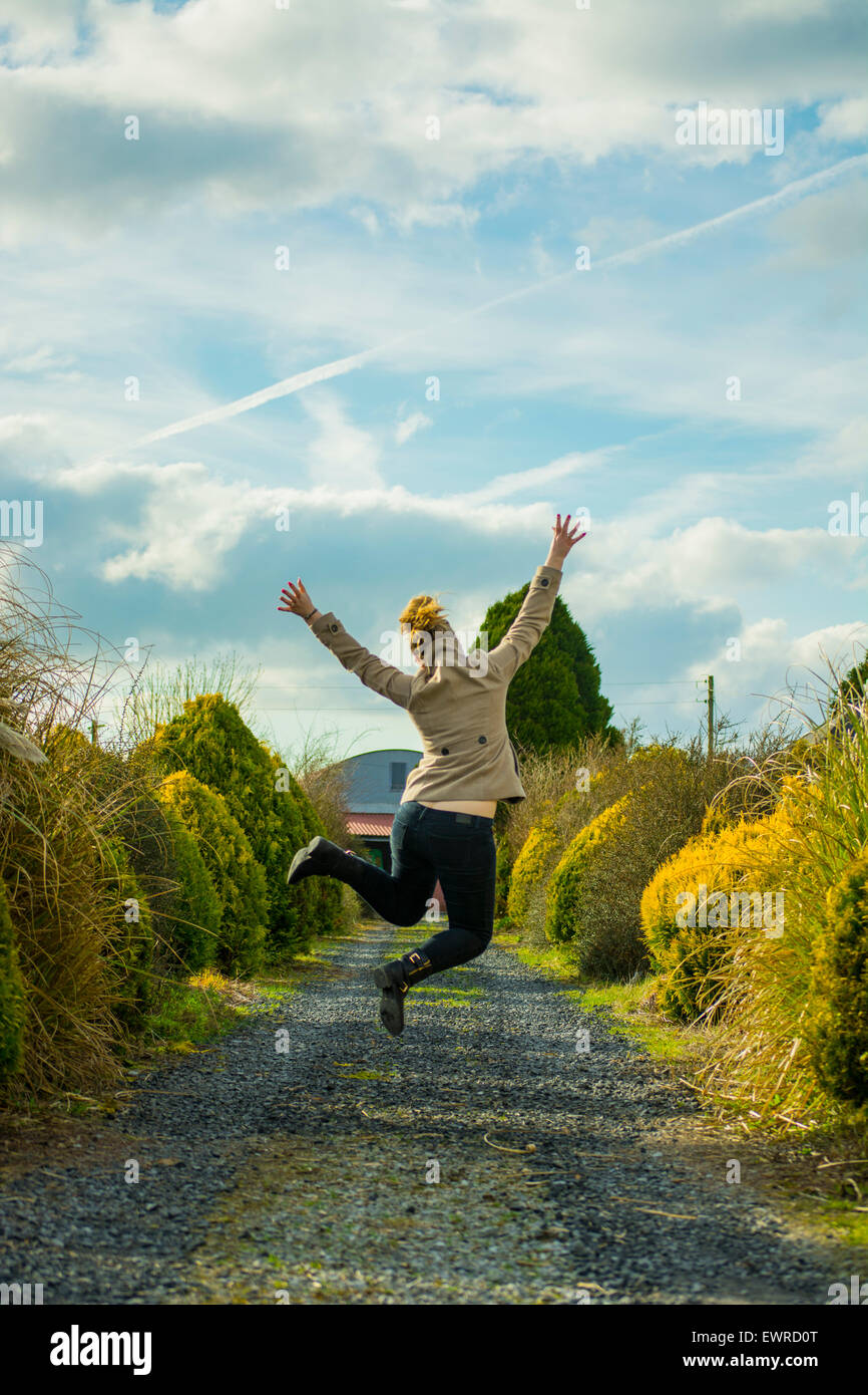 Happy Girl, woman, lady, female in a coat leaping in the air jumping with hands up on a country lane, blue sky and - Stock Image