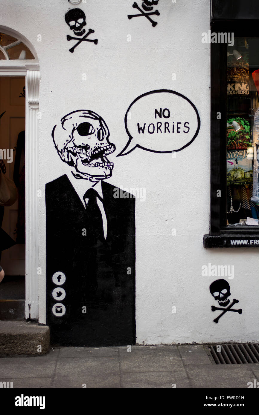 Graffiti artwork of a Skull in a suit with speech bubble 'no Worries' on a wall on a wall in Temple bar, - Stock Image