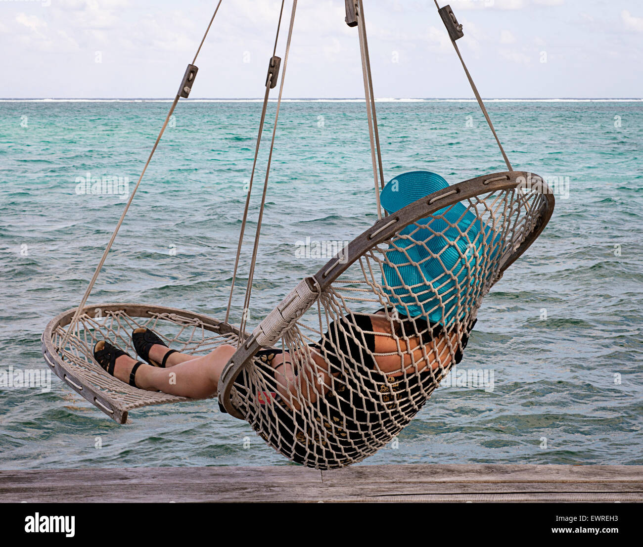 A woman in a hammock chair in Belize - Stock Image